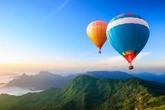 Globos de aire caliente coloridos que vuelan sobre la montaña Fotografía de archivo