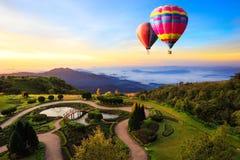 Globos de aire caliente coloridos que vuelan sobre la montaña Imagenes de archivo