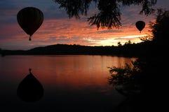 Globos de aire caliente sobre el agua en la salida del sol de la puesta del sol Imagen de archivo