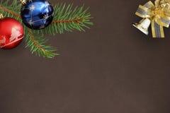 Globos del abeto de la rama de la Navidad, azules y rojos, campana decorativa encendido Fotos de archivo