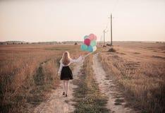 Globos del adolescente en campo del verano Imagen de archivo