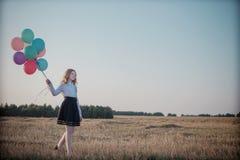 Globos del adolescente en campo del verano Fotos de archivo