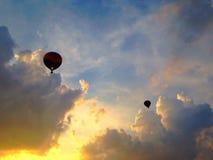 Globos del aire caliente en la puesta del sol Imagenes de archivo
