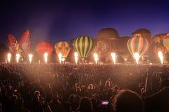 Globos del aire caliente que brillan intensamente en la noche, delante de la muchedumbre enorme fotografía de archivo libre de regalías