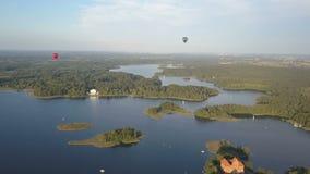 Globos del aire caliente que vuelan sobre los lagos y las islas hermosos en Lituania cerca del castillo de Trakai en verano Silue metrajes