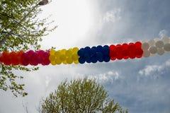 Globos del color en aire entre los árboles Fotografía de archivo