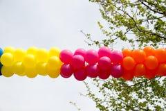 Globos del color en aire entre los árboles Foto de archivo