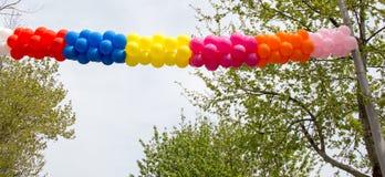 Globos del color en aire entre los árboles Imagenes de archivo