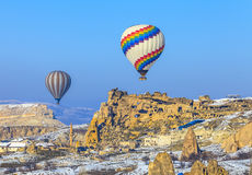 Globos del vuelo sobre las montañas en la puesta del sol Capadocia Turquía Fotografía de archivo libre de regalías
