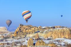 Globos del vuelo sobre las montañas en la puesta del sol Capadocia Turquía Imagen de archivo libre de regalías