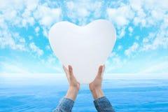 Globos en forma de corazón en las manos Imágenes de archivo libres de regalías