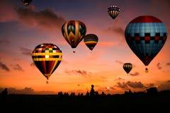 Raza del globo en la salida del sol Imagen de archivo libre de regalías