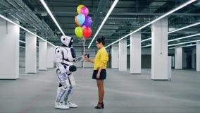 Globos gifting de una muchacha a un robot en un cuarto almacen de video