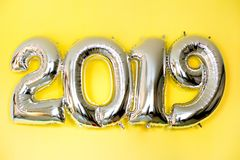 Globos inflables de plata en la forma de los números 2019 en el fondo amarillo imagenes de archivo