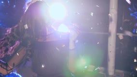 Globos inflables en los brazos de la hembra agraciada en contraluz en la iluminación del confeti y del reflector en el banquete metrajes