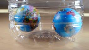 Globos pequenos do mundo que caem dentro de uma garrafa de água plástica video estoque