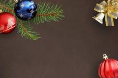 Globos rojos del abeto de la rama de la Navidad, azules y ondulados, campana decorativa Imágenes de archivo libres de regalías