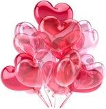 Globos rosados del partido en forma como corazones Foto de archivo