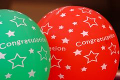 Globos verdes rojos con la enhorabuena de la palabra y una muestra de la estrella imagen de archivo libre de regalías