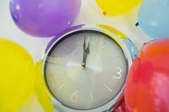 Globos y manos de reloj que alcanzan medianoche del reloj de 12 o Fotografía de archivo libre de regalías