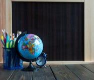 Globus, pulso de disparo e artigos de papelaria pequenos na tabela de madeira na frente do quadro Conceito do estudo fotografia de stock