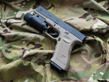 Glock 17 9mm semi-automatic pistol. Los Angeles, CA, USA - September 11, 2015: Glock 17 semi-automatic 9x19mm pistol and a Multicam pattern background Royalty Free Stock Photography
