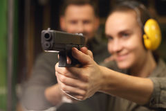 Glock, woman shoots at the shooting range. Woman takes lessons in shooting with a handgun on the shooting range royalty free stock image