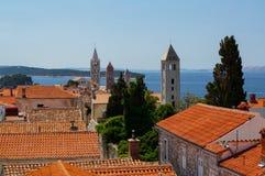 Glockentürme und mit Ziegeln gedeckte Dächer von Rab Town, Kroatien Stockbilder