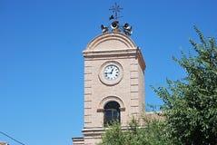 Glockenturm der Kirche mit der eingebetteten Uhr, welche die Stunden wählt stockbilder