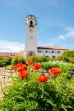 Glockenturm eines Zugdepots mit Leuchtorangemohnblumen Lizenzfreie Stockfotos