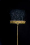 Gloden small cooper broom on black background Royalty Free Stock Photos