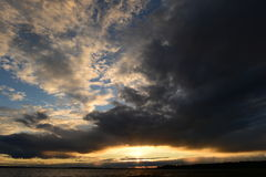Gloed van zonlicht in de donkere wolken van de hemel bij zonsondergang Stock Foto