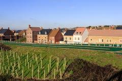 Gloednieuwe huizen door een dijk met bomen die voor lawaai r worden geplant Stock Afbeeldingen