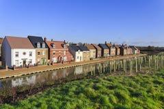Gloednieuwe luxehuizen door een kanaal met geplante bomen Stock Afbeelding
