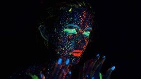 Gloedverf op het gezicht van het meisje Portret van een mooie jonge vrouw met gloeiende verf op haar gezicht stock videobeelden