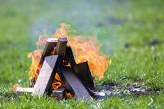 Gloeiend vuur op aard Buiten brandend houten planken op de zomerdag Heldere oranje vlammen, lichte rook en donkere as op groen stock afbeelding