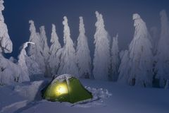 Gloeiende groene het kamperen tent in sneeuwbergen in het de winterbos in een sprookje Reis door de de winter alpiene bossen stock foto