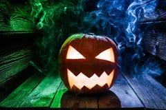 Gloeiende pompoenen voor Halloween met blauwe en groene rook op houten bureau Stock Foto