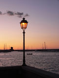 Gloeiende straatlantaarn in de haven, bij zonsondergang Stock Afbeeldingen
