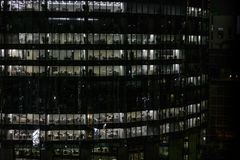 Gloeiende vensters van wolkenkrabbers bij avond - Mening van moderne bureaus in een gebouw royalty-vrije stock afbeeldingen
