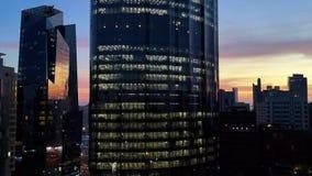 Gloeiende vensters van wolkenkrabbers bij een bewolkte zonsondergang - Weergeven van moderne bureaus en wolkenkrabbers stock videobeelden
