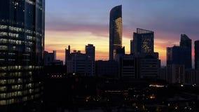 Gloeiende vensters van wolkenkrabbers bij een bewolkte zonsondergang - Weergeven van moderne bureaus en wolkenkrabbers stock video