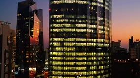 Gloeiende vensters van wolkenkrabbers bij zonsondergang - Mening van moderne bureaus en torens stock footage