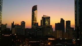 Gloeiende vensters van wolkenkrabbers bij zonsondergang - Mening van moderne bureaus en torens, Abu Dhabi stock videobeelden