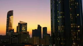 Gloeiende vensters van wolkenkrabbers bij zonsondergang - Mening van moderne bureaus en torens, Abu Dhabi