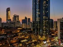 Gloeiende vensters van wolkenkrabbers bij zonsondergang - Mening van moderne bureaus en torens, Abu Dhabi stock foto's