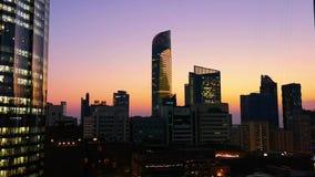 Gloeiende vensters van wolkenkrabbers bij zonsondergang - Mening van moderne bureaus en torens, Abu Dhabi stock video