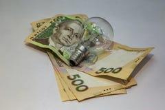 Gloeilamp en geld op witte achtergrond Energie - besparing stock foto