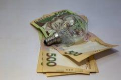Gloeilamp en geld op witte achtergrond Energie - besparing royalty-vrije stock foto's