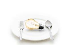 Gloeilamp in plaat en vork en lepel op wit wordt geïsoleerd dat Royalty-vrije Stock Foto